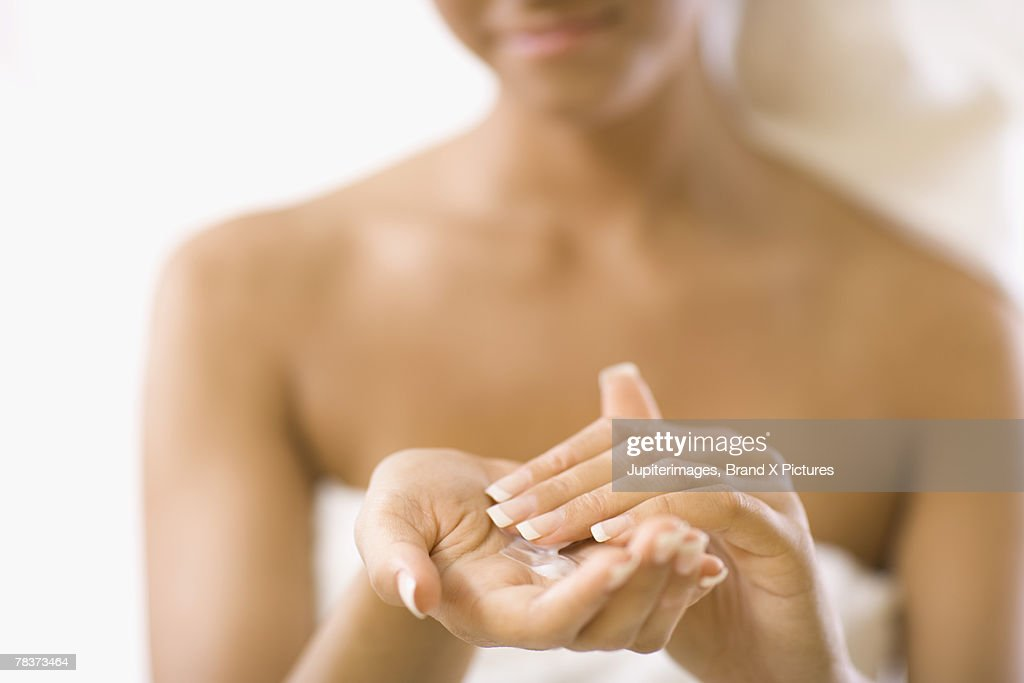 Young woman with lotion in hands : ストックフォト