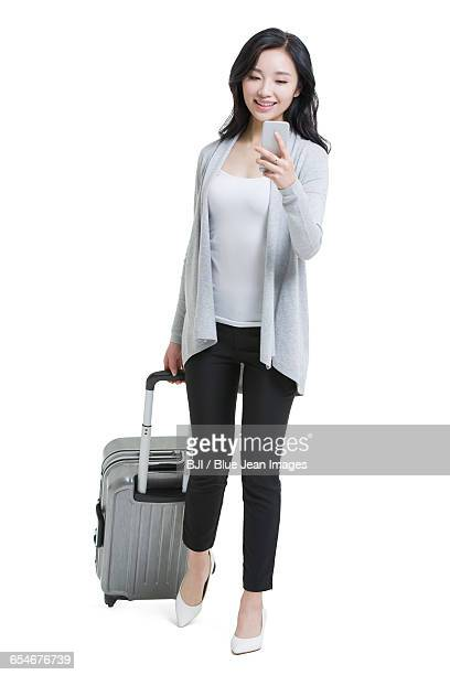 Young woman with luggage and smart phone