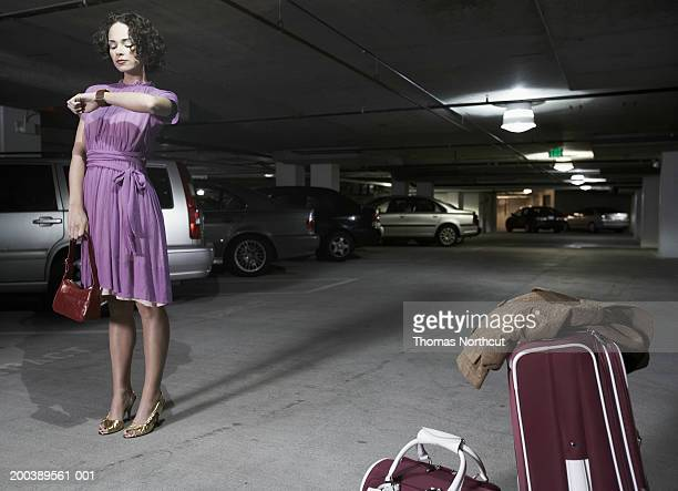 young woman with luggage looking at watch in parking garage - purple dress stock pictures, royalty-free photos & images