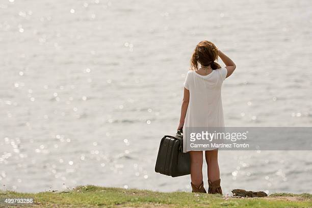 Young woman with luggage standing in hill, rear view