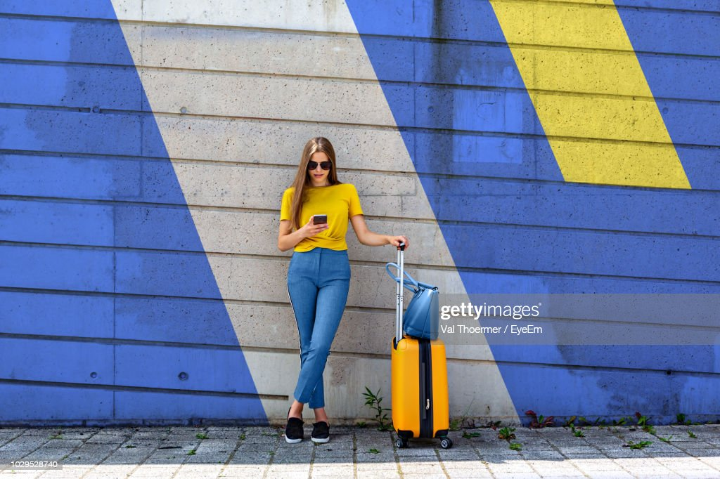 Young Woman With Luggage Using Mobile Phone While Standing Against Wall : Foto de stock