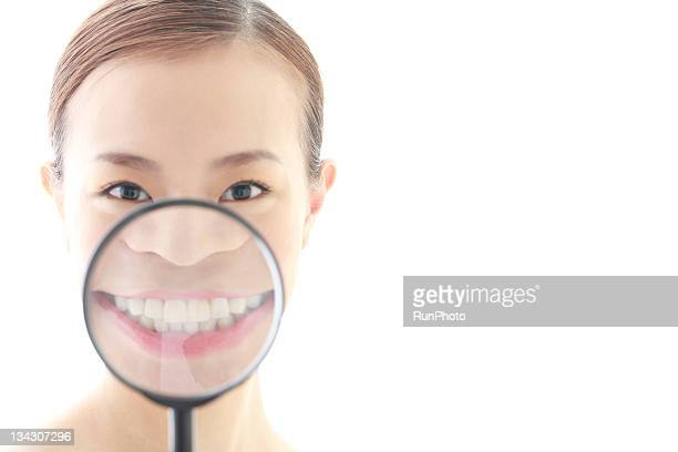 young woman with magnifying glass,teeth close-up