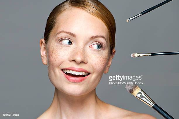 Young woman with make-up brushes