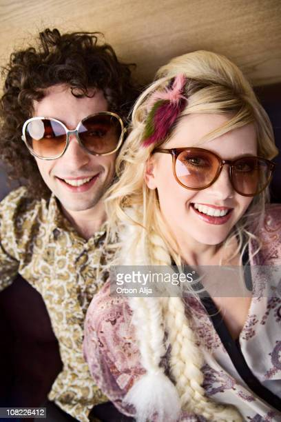 Young Woman with Man Smiling and Wearing Large Retro Sunglasses