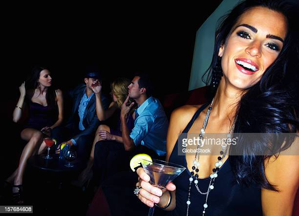 Young woman with martini glass and her friends in background