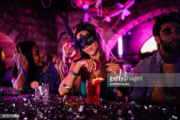 young woman with mask at mardi gras night club party - new orleans mardi gras stock photos and pictures