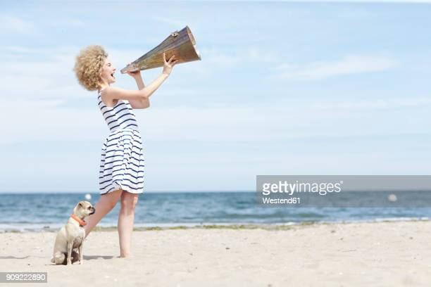 Young woman with megaphone and dog on the beach