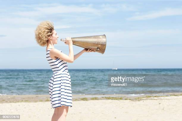 young woman with megaphone on the beach - megaphone stock pictures, royalty-free photos & images