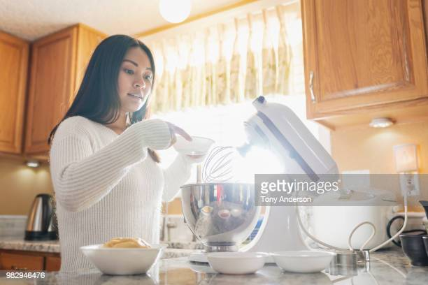 Young woman with mixer baking in home kitchen