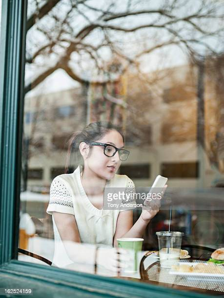 Young woman with mobile device in window of cafe