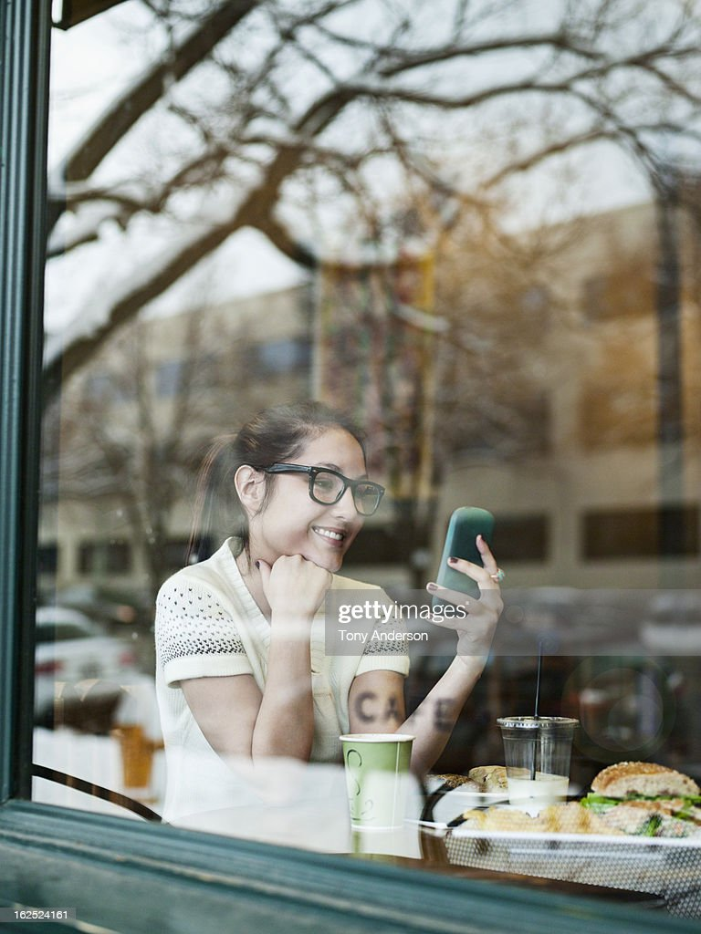 Young woman with mobile device in window of cafe : Stock Photo
