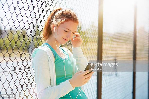 young woman with mobile on outside tennis court - 網状 ストックフォトと画像
