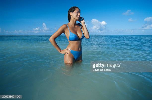Young woman with mobile phone in water