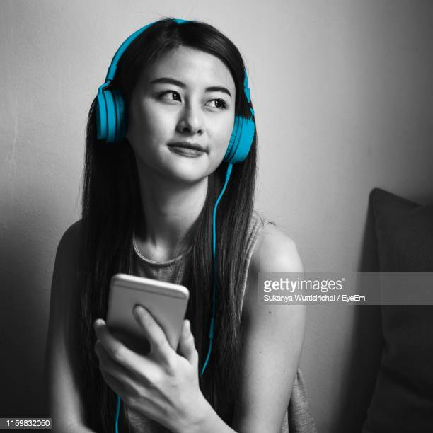 young woman with mobile phone listening music against wall at home - isolated color stock pictures, royalty-free photos & images