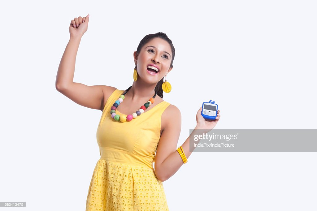 Young woman with mobile phone rejoicing : Stock Photo