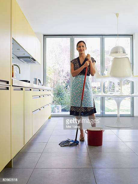 Young woman with mop in kitchen