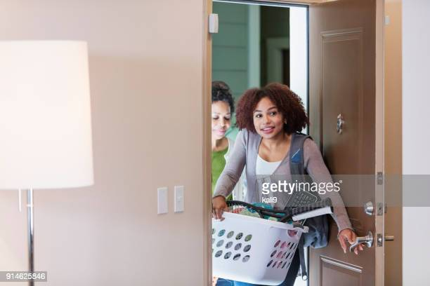 young woman with mother, moving into apartment - arrival stock pictures, royalty-free photos & images
