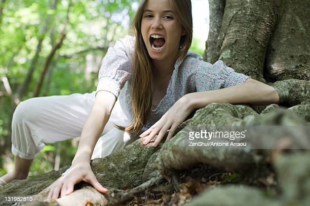 Young woman with mouth open climbing on roots of tree