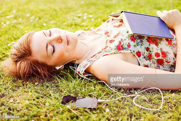 Young woman with mp3 player and book.