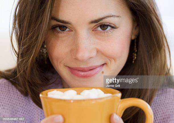 Young woman with mug of hot chocolate with marshmallows, smiling, close-up, portrait