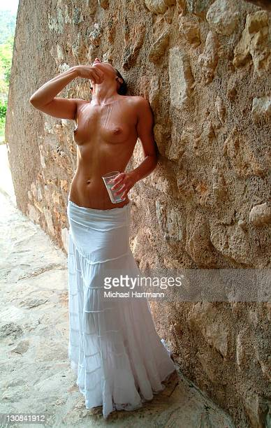 Young woman with naked upper body and white skirt refreshing her skin with water, Majorca, Spain