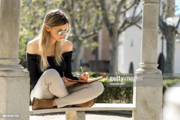 young woman with notebook sitting on bench writing down something - linkshandig stockfoto's en -beelden