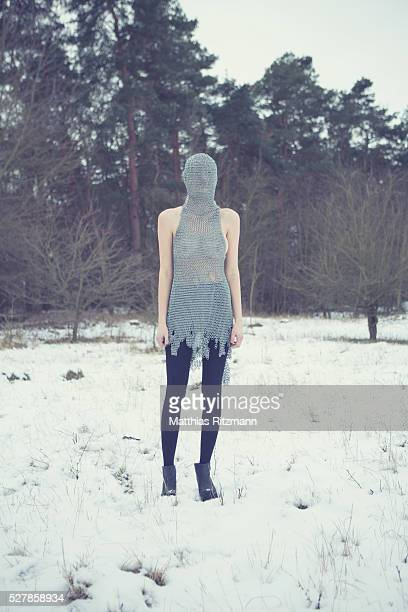 Young woman with obscured face standing on snowy field