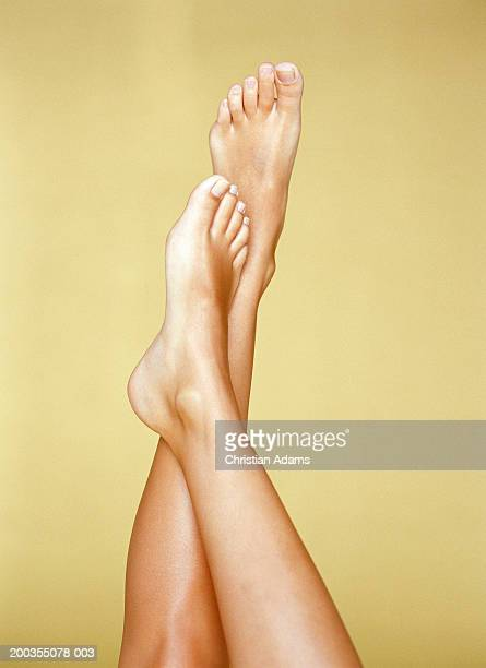 young woman with one foot resting on shin of other, close-up - legs crossed at ankle stock pictures, royalty-free photos & images