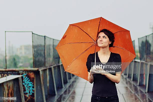 young woman with orange umbrella in the rain - umbrella stock pictures, royalty-free photos & images