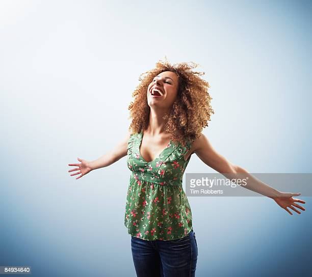 Young woman with outstretched arms, laughing