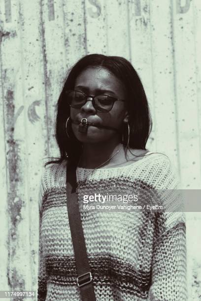 young woman with padlock on mouth standing against wall - myra dunoyer vahighene photos et images de collection