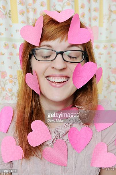 Young woman with paper hearts all over her.