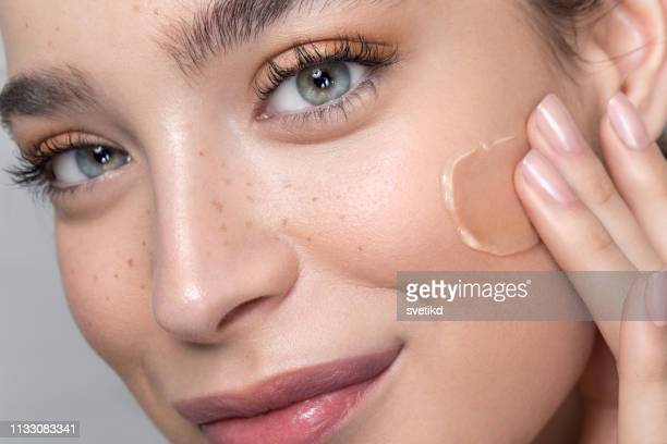 young woman with perfect skin applying foundation - beauty stock pictures, royalty-free photos & images