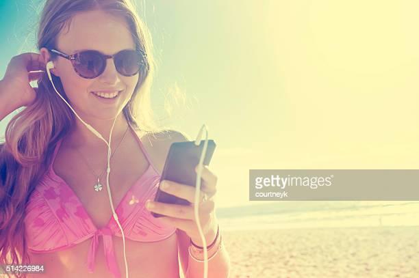 Giovane donna con telefono, gli auricolari in spiaggia