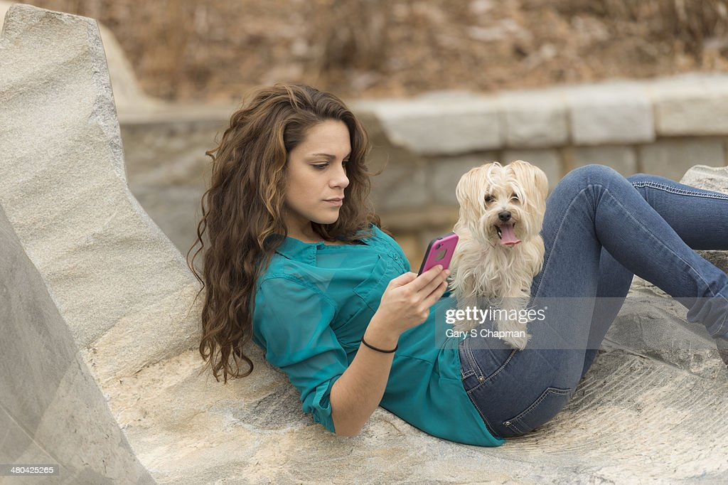 Young woman with phone and morkie dog : Stock Photo