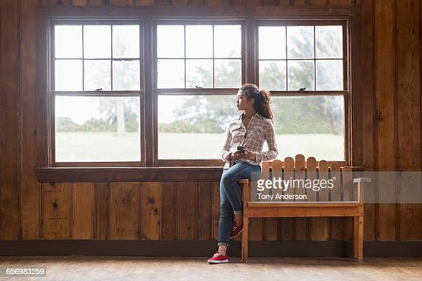 Young woman with phone in rustic lodge