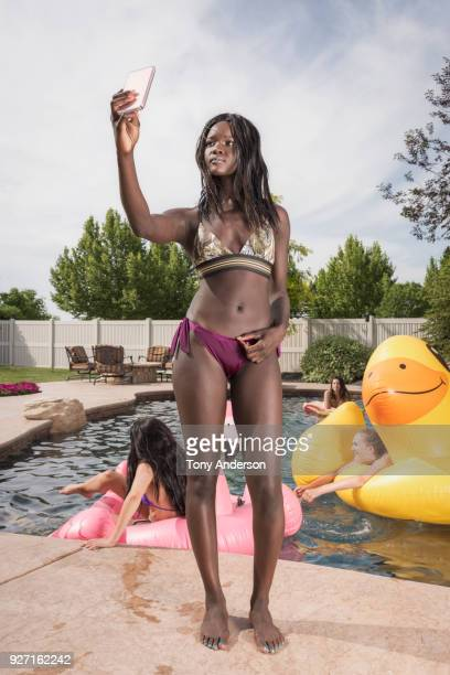 young woman with phone standing by swiming pool - ado en maillot de bain photos et images de collection