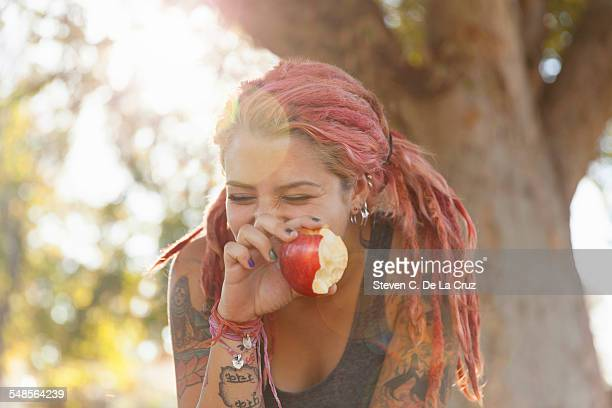Young woman with pink dreadlocks giggling whilst eating apple in park