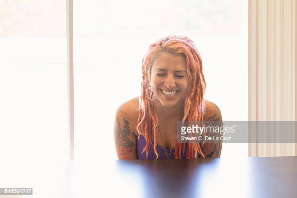 Young woman with pink dreadlocks laughing