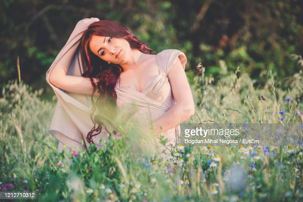 young woman with pink flowers on field - bogdan negoita stock pictures, royalty-free photos & images