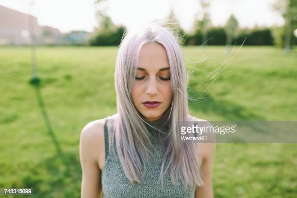 Young woman with pink grey hair on a meadow