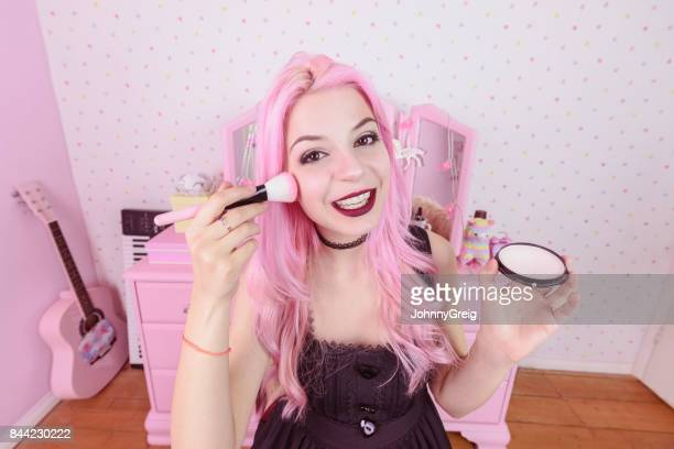 Young woman with pink hair applying blusher towards camera