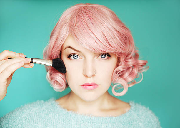 Young woman with pink hair putting on blusher