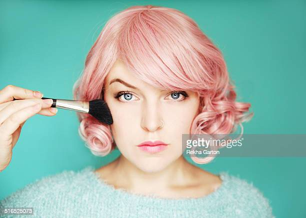 young woman with pink hair putting on blusher - rekha garton stock pictures, royalty-free photos & images