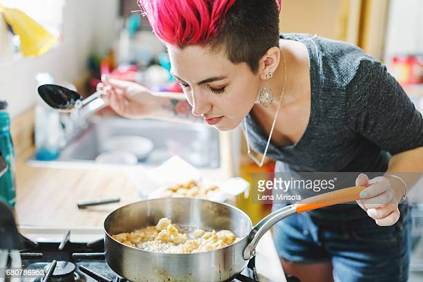 Young woman with pink hair smelling fried food on kitchen hob