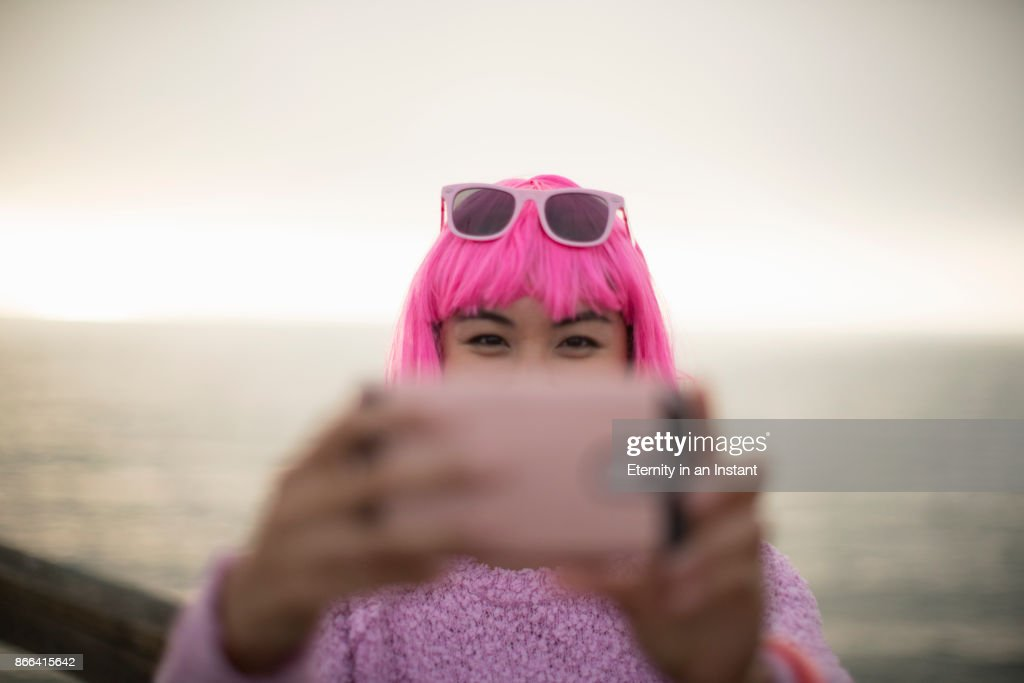 Young woman with pink hair taking a photo with her mobile phone : Stock Photo