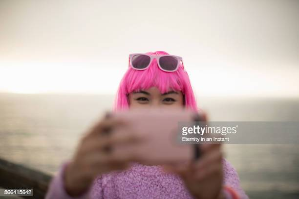 Young woman with pink hair taking a photo with her mobile phone