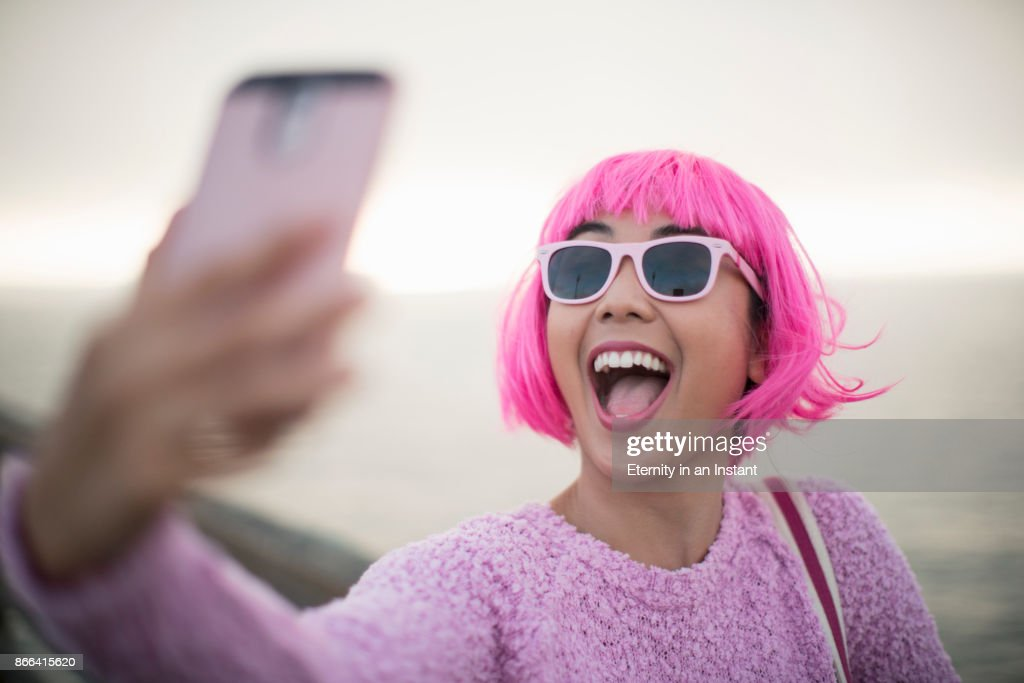 Young woman with pink hair taking a selfie : Stock Photo