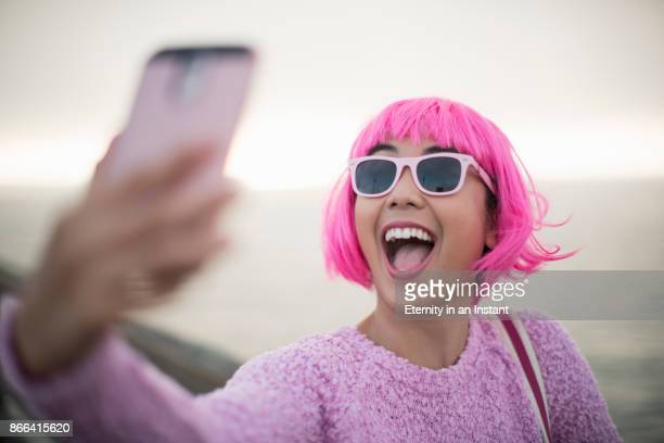 young woman with pink hair taking a selfie - millennial generation stock pictures, royalty-free photos & images