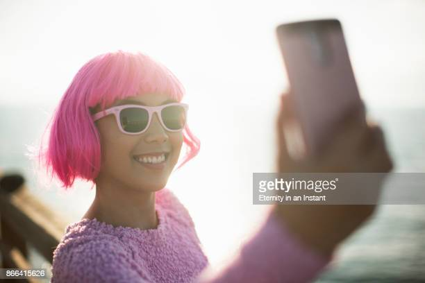 young woman with pink hair taking a selfie - fringe stock pictures, royalty-free photos & images